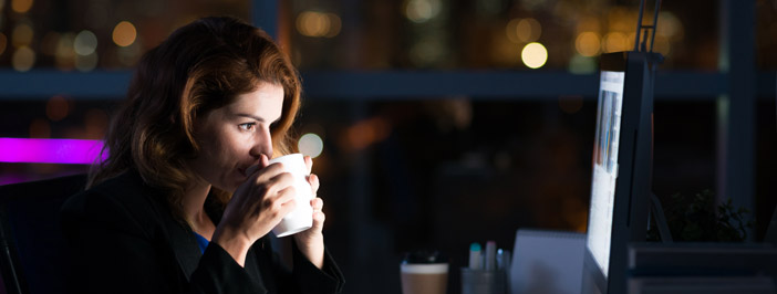 Woman drinking coffee as she works on the computer at night