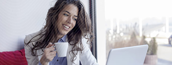 woman smiling drinking coffee and using laptop