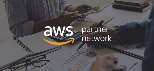 People working on desk with AWS logo on top of it